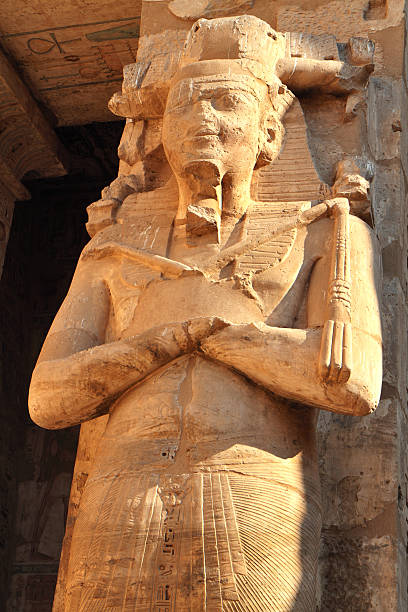 """Osiride Statue of Ramesses III, Medinet Habu, Luxor, Egypt. """"Osiride statue of Ramesses III, First Court of Medinet Habu, Theban Necropolis, Luxor, Egypt.  Medinet Habu is the mortuary temple of the 12th century BC pharaoh Ramesses III (also Ramses, Rameses and Usermaatre-meryamun).  Located on the West Bank in the southern part of the Theban necropolis, Medinet Habu is one of the finest temples in Egypt."""" Tomb Of Ramses III stock pictures, royalty-free photos & images"""