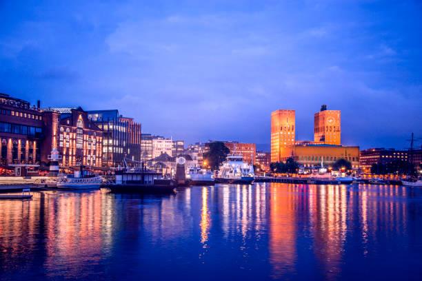 oslo aker brygge haven en stadhuis nachts, noorwegen - oslo city hall stockfoto's en -beelden