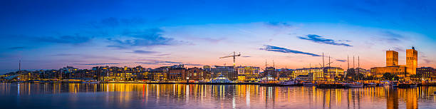 Oslo Aker Brygge harbour waterfront landmarks illuminated sunset panorama Norway Summer sunset skies over the illuminated landmarks of Oslo's downtown waterfront, from the busy bars and restaurants of Aker Brygge, the popular leisure district, to the iconic twin towers of City Hall, Radhus, and the crowded marina on the tranquil waters of OsloFjorden, Norway. ProPhoto RGB profile for maximum color fidelity and gamut. oslo stock pictures, royalty-free photos & images