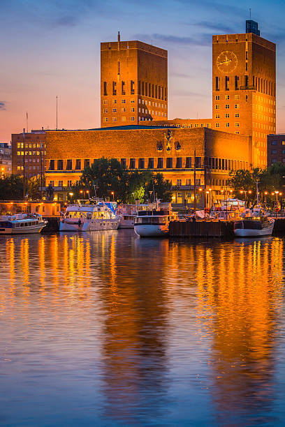 oslo iconic towers city hall overlooking tranquil sunset harbour norway - oslo city hall stockfoto's en -beelden