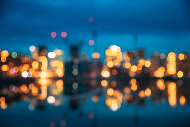 Oslo, Norway. Night Abstract Boke Bokeh Background Effect. Design Backdrop. Night View Embankment And Residential Multi-storey House In Gamle Oslo District. Residential Area Reflected In Sea Waters stock photo