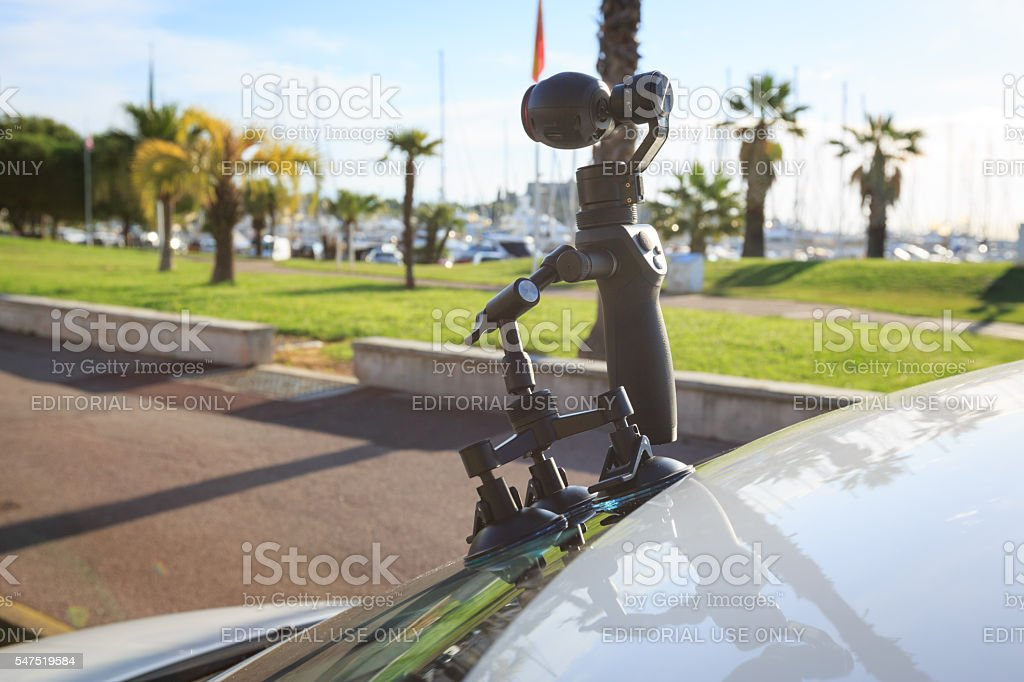 DJI Osmo handheld gimbal camera mounted on a car's windshield stock photo