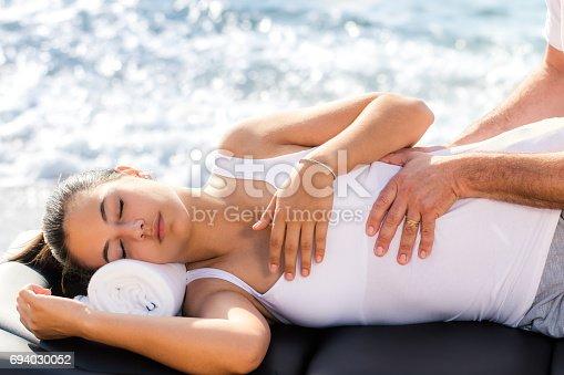 istock Osteopath doing manipulative treatment on female torso outdoors. 694030052