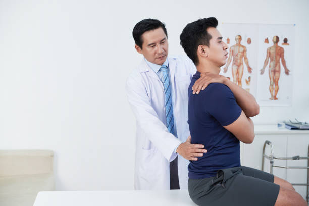 osteopath palpating back - osteopathy stock pictures, royalty-free photos & images