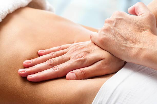 osteopathic bauch massage. - chiropraktik wellness stock-fotos und bilder