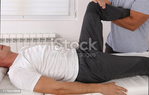 istock Osteopathy treatment. Therapist treating injured knee of athlete male patient . Sport physical therapy concept 1175325808