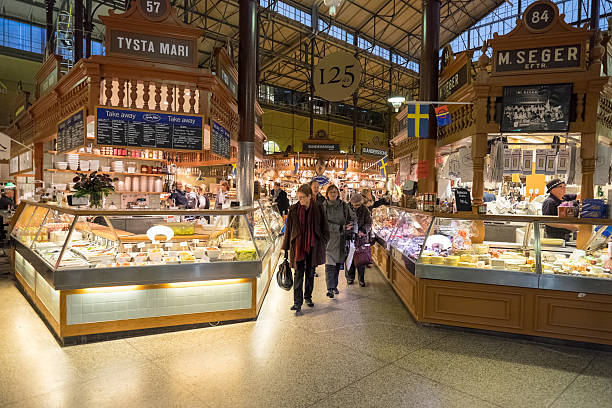 Ostermalm market hall, Stockholm Stockholm, Sweden – November 10, 2014: Customers stroll in Ostermalm market hall in Stockholm. The famous Ostermalm market hall was opened in 1888. market hall stock pictures, royalty-free photos & images
