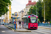 Ostrava, Czech Republic - July 4, 2016:  view showing Ostrava tram station, tram in the tramway, buildings, trees and passengers waiting in the station can be seen on the background