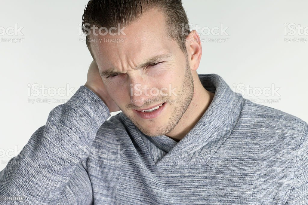 Young man with an ear infection over a white background