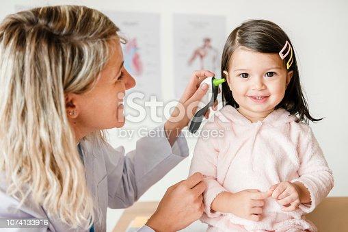 Otolaryngologist checking up on a sweet little girl
