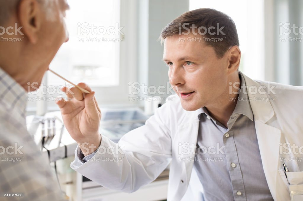Otolaryngologist examines sore throat of senior patient stock photo