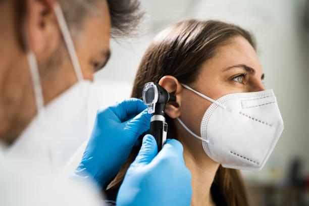 Otolaryngology Doctor Examining Patient Ear stock photo