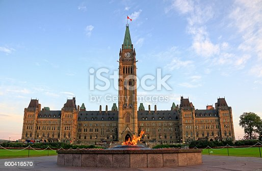 Centennial Flame in front of Canadian Parliment Building Peace Tower and Centre Block on Parliament Hill, Ottawa, Canada. Parliament Building was lit by morning sun light under blue sky and white clouds