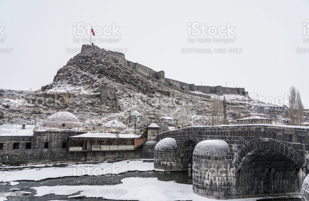 Ottoman bridge and castle on frosted river in Kars city in Turkey stock photo