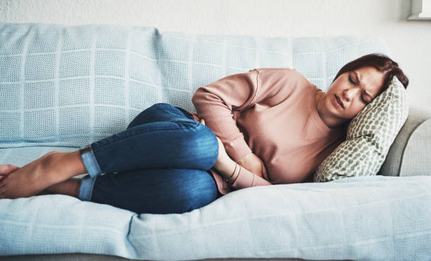 Ouch! My tummy! Cropped shot of an attractive young woman lying on her sofa alone and suffering from period cramps at home styles stock pictures, royalty-free photos & images