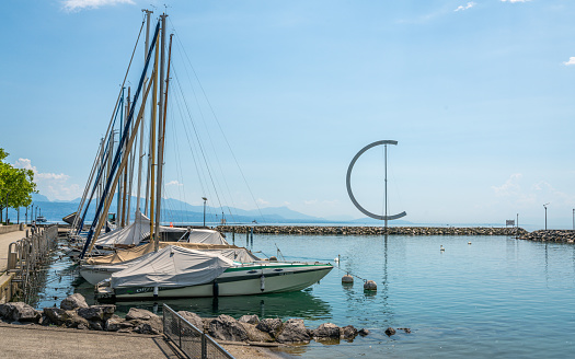 Ouchy port marina and Lake Geneva view with boats and giant weather vane in Lausanne Switzerland