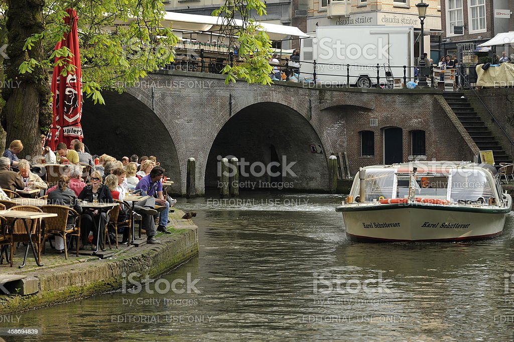 Oudegracht with outdoor restaurant and a tourboat royalty-free stock photo