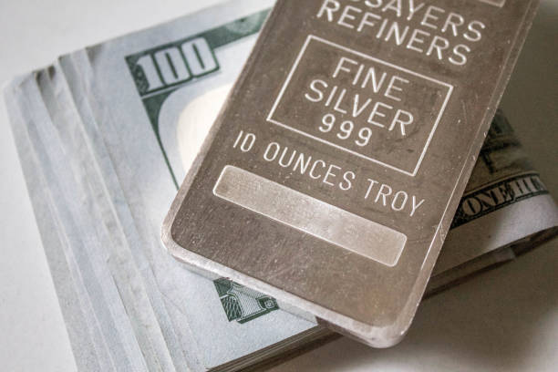 10 Ounce Silver Bar Over Stack of Hundred Dollar Bills stock photo
