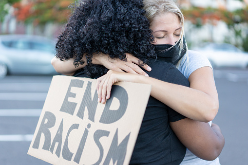 oung african woman hugging a white northern woman after a protest - Northern woman with end racism bannner in her hands - Concept of no racism