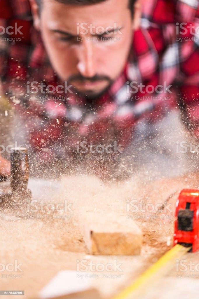 oung handosme carpenter blowing off sawdust stock photo