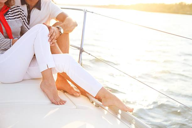 Сouple stting on sailboat deck in the sea - Photo