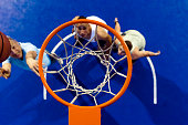 High angle view of three young men playing basketball. Photo of Caucasian basketball players playing basketball on the court. Competition concept with people who playing and exercise basketball sport in school gym.