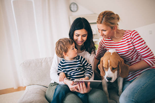 Our cute family Photo of family, two women, dog and cute little boy, are sitting on the sofa in their living room and using tablet gay couple stock pictures, royalty-free photos & images