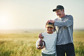 Shot of father and son playing with a football on a field