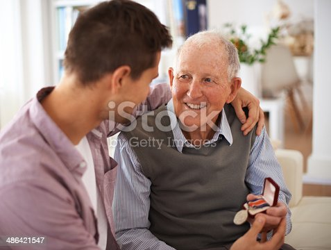 Shot of a senior father giving his son a medal while they're sitting indoorshttp://195.154.178.81/DATA/i_collage/pi/shoots/783272.jpg