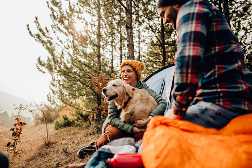 Photo of a young couple and their dog camping in the woods on a beautiful autumn day; spending time outdoors and appreciating nature.
