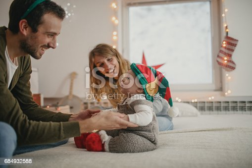 Photo of a young family with one child, celebrating the first Christmas they are spending together with a baby
