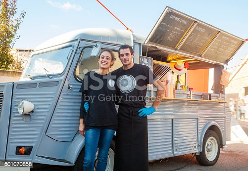 Young and happy couple posing in front f ther food truck restaurant.