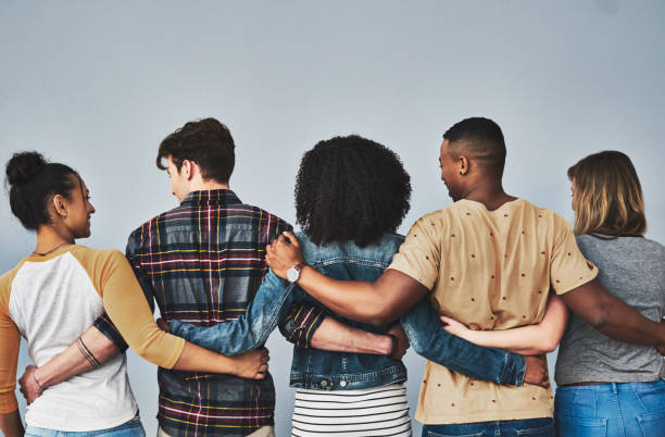 Our friends become our family Rearview studio shot of a diverse group of young people embracing each other against a gray background people in a row stock pictures, royalty-free photos & images