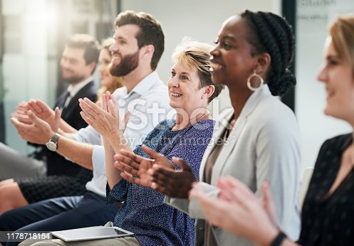 Shot of a mature businesswoman clapping and celebrating with other entrepreneurs at a business conference