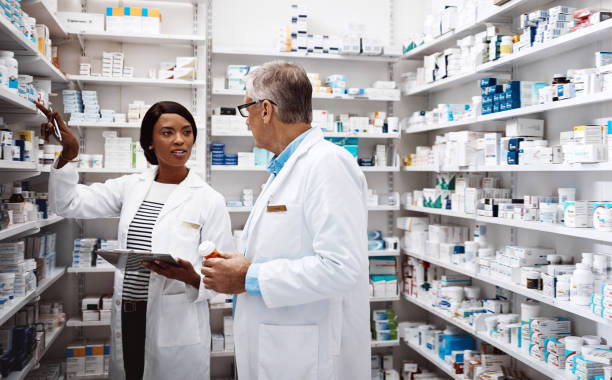 Our help goes beyond prescriptions Shot of two pharmacists working together in a drugstore pharmacist stock pictures, royalty-free photos & images