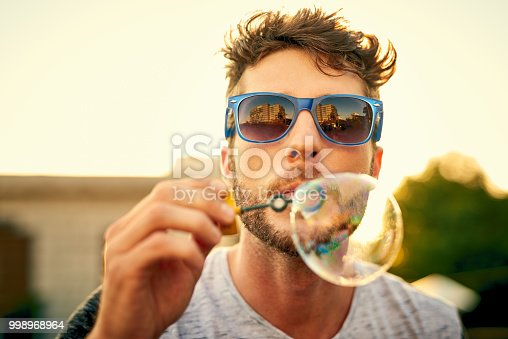 Shot of a young man blowing bubbles outdoors