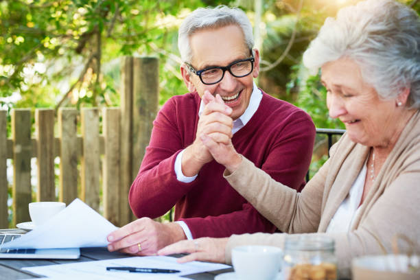 Our investments just keep growing Cropped shot of a senior couple high fiving while going over their finances while sitting outside grounds stock pictures, royalty-free photos & images