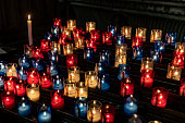 Notre Dame de Fourviere votive candles in Lyon, France. The image is sharp with slight movement on the flames and exposed for the candles to give a black bacjground.