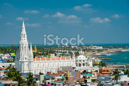 Our Lady of Ransom Shrine Church behind colorful houses on a sand beach occupied by fishing boats in Kanyakumari in India