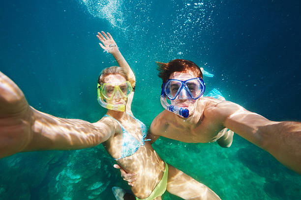 Our love is under pressure... Shot of a young couple snorkelling in crystal clear water snorkel stock pictures, royalty-free photos & images