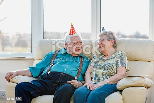 Senior Caucasian couple sat on their sofa in their conservatory both wearing party hats and smiling.
