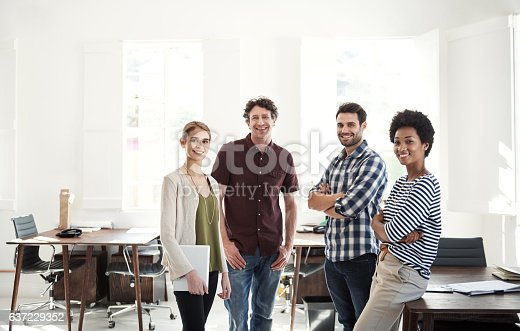 Portrait of a team of designers standing together in an office