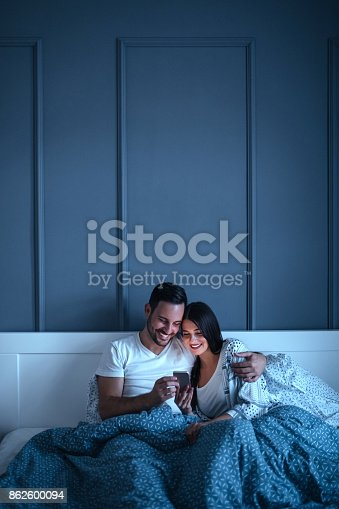 Young couple cuddling in bed while browsing the internet on their phone.