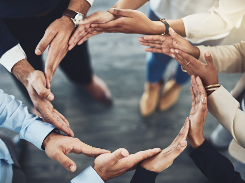 Closeup of a group of unrecognizable businesspeople holding hands in a certain way to form a circle inside of the office