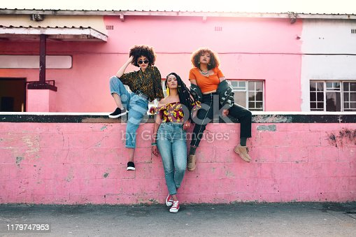 Full length shot of three attractive and stylish young women posing together against an urban background