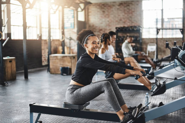 Our sweat session is in full swing Shot of a young woman working out with a rowing machine in the gym exercise machine stock pictures, royalty-free photos & images