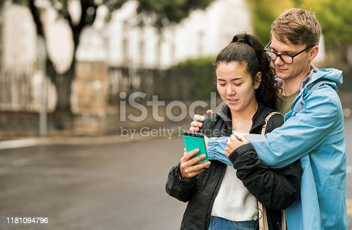 Shot of a young couple standing outdoors and looking at mobile phone on a rainy day