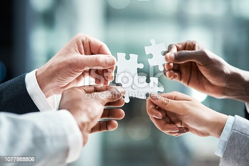 Closeup shot of a group of unrecognizable businesspeople holding puzzle pieces together