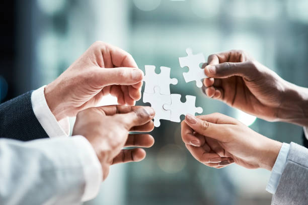 Our team makes for the perfect fit Closeup shot of a group of unrecognizable businesspeople holding puzzle pieces together jigsaw piece stock pictures, royalty-free photos & images