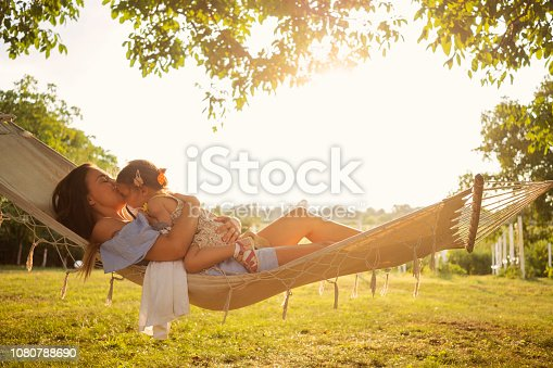 Mother and daughter enjoying in hammock